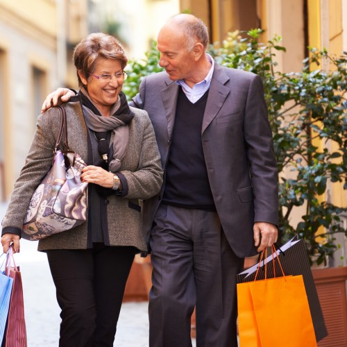 A happy, old couple walking together holding shopping bags.